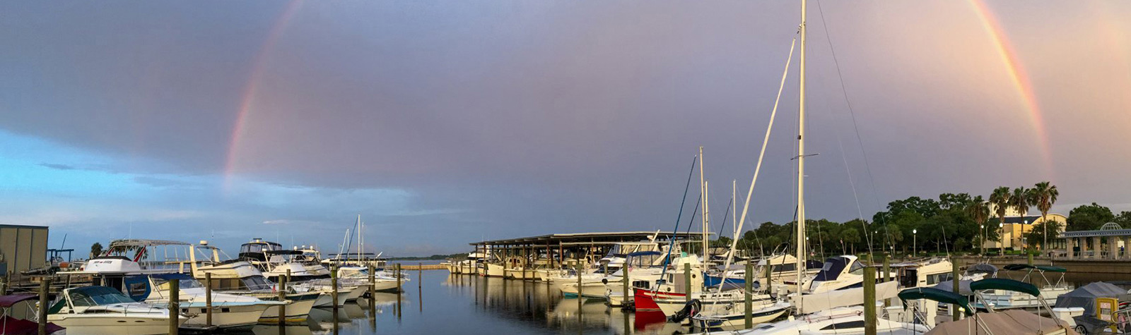 boats at dock with a rainbow in the harbor